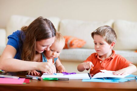 Young mother and her two kids drawing together. Can be used also in kindergarten/daycare context Stock Photo - 5604529