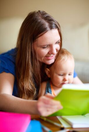 Young mother and her baby daughter reading together. Can be used also in kindergartendaycare context.