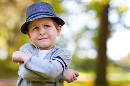 Stylish young boy in gray hat outdoors at autumn day photo