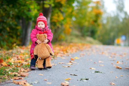 Adorable baby girl walking outdoors with teddy bear at beautiful sunny autumn day photo