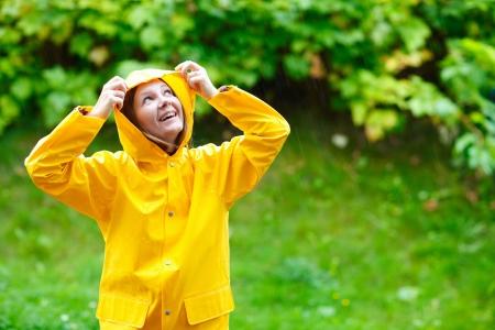 estaciones del año: Mujer joven feliz en impermeable amarillo bajo la lluvia