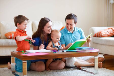 Young happy family with two kids drawing and reading together photo