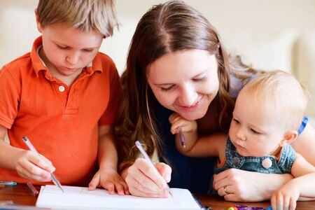 Young mother and her two kids drawing together. Can be used also in kindergarten/daycare context Stock Photo - 5635825