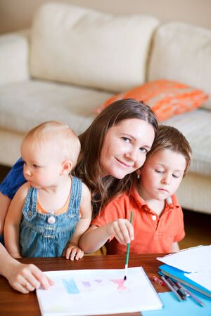 Young mother and her two kids drawing together. Can be used also in kindergartendaycare context. photo
