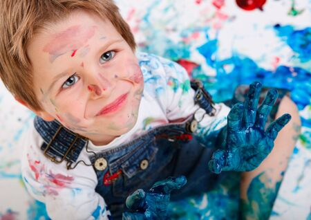 Portrait of cute 5 years old boy painting on white background Stock Photo - 5774482