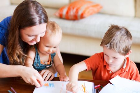 Young mother and her two kids drawing together. Can be used also in kindergartendaycare context photo
