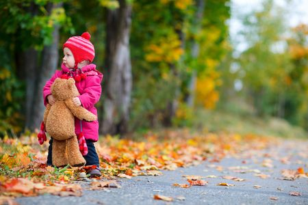 pink teddy bear: Cute 1 year old girl walking outdoors at autumn day