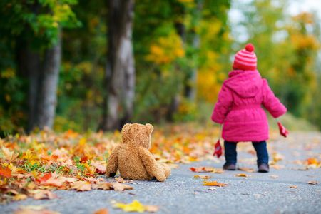 pink teddy bear: Cute 1 year old girl walking outdoors at autumn day. Focus on teddy bear Stock Photo