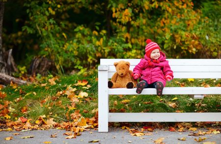 sitting ground: Cute 1 year old girl outdoors at autumn day Stock Photo