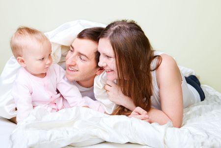 papa y mama: Felices los j�venes padres con su hija en el dormitorio