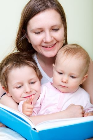 Young mother with her two kids reading book in bed Stock Photo - 5849949