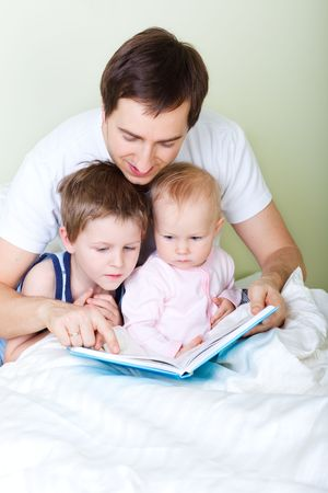Young father and two kids reading book in bed Stock Photo - 5849941