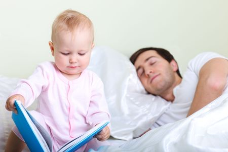 Adorable 1 year old girl reeding book to sleeping father photo