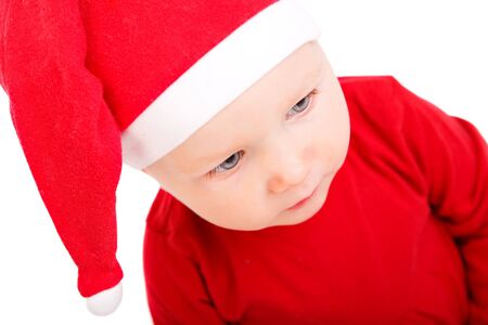 Portrait of Christmas baby girl in red Santa hat, isolated on white photo