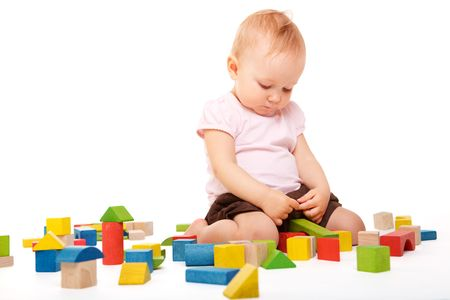 Cute baby girl building with colorful wooden blocks. Isolated on white background. photo
