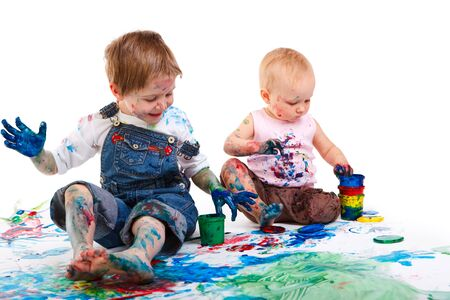 Cute 5 years old boy and toddler girl painting on white background photo
