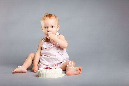 Cute little girl eating her first birthday cake photo