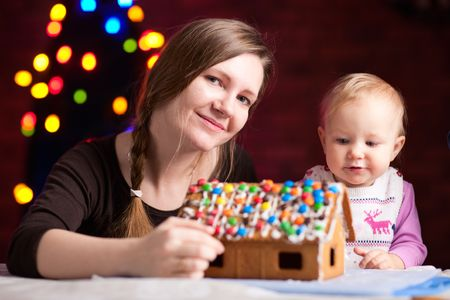 Family decorating gingerbread house at Christmas eve photo