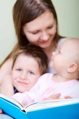 Young mother with her two kids reading book in bed. Focus on book. Stock Photo - 5938471