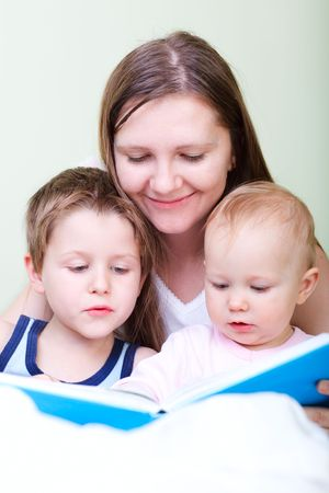 Young mother with her two kids reading book in bed photo