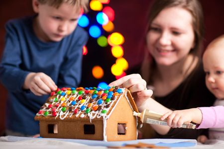 home decorating: Family decorating gingerbread house on Christmas eve. Focus on house Stock Photo