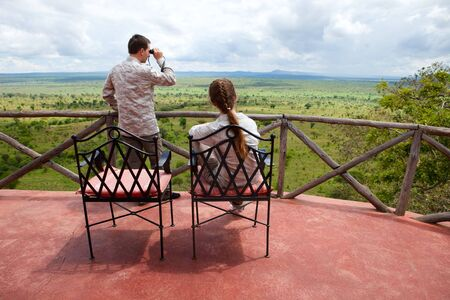arial views: Safari vacation. Young couple in safari clothes observing beautiful national park of Tarangire in Tanzania from balcony in lodge.