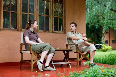 Safari vacation. Young couple in safari clothes sitting in front of their lodge room. Stock Photo - 6192479