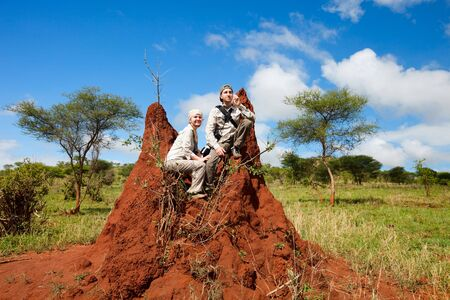 Safari vacation. Couple sitting on termite mount in Tarangire national park, Tanzania. Stock Photo - 6192484