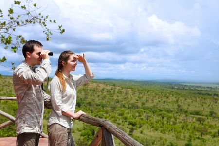 lodging: Safari vacation. Young couple in safari clothes observing beautiful national park of Tarangire, Tanzania from balcony in lodge.