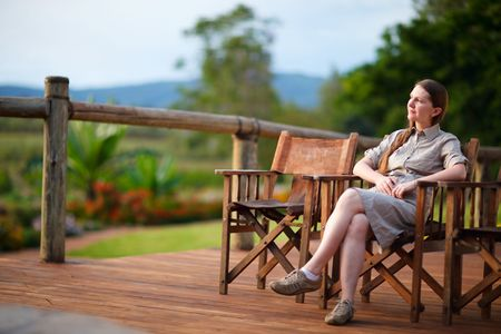 lodges: Safari vacation. Young beautiful woman enjoying evening in safari lodge.