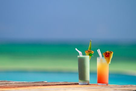 Two tropical cocktails near swimming pool and beach photo