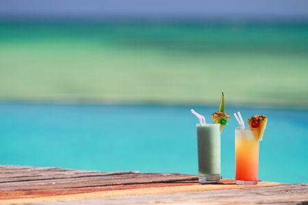 Twee tropische cocktails buurt zwembad en strand