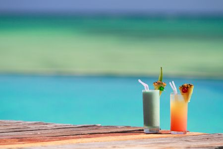 pool party: Two tropical cocktails near swimming pool and beach
