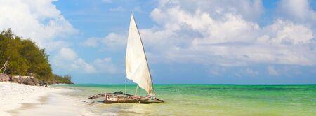 Panoramic photo of white sand tropical beach and traditional Zanzibar boats photo