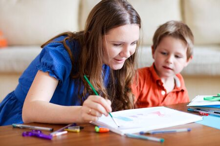 context: Young mother and her two kids drawing together. Can be used also in kindergartendaycare context