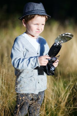 Trendy small boy with retro camera photographing outdoors at sunny autumn day photo