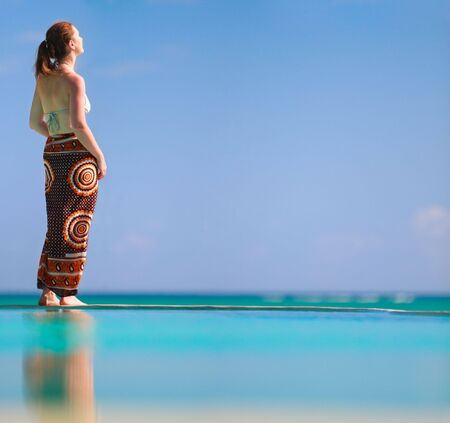 Beautiful woman relaxing by infinity swimming pool