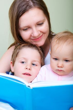 Young mother with her two kids reading book in bed Stock Photo - 6436410