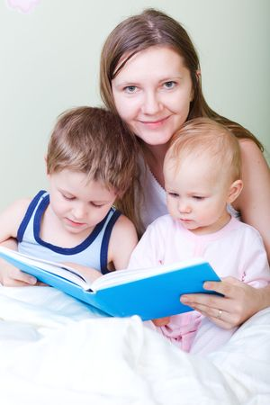 Young mother with her two kids reading book in bed Stock Photo - 6436420