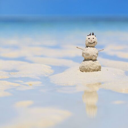 Snowman made from white tropical sand on exotic beach with ocean on background. photo