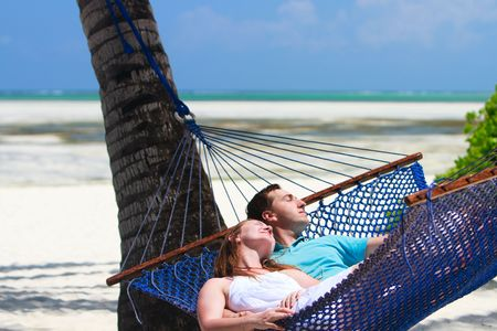 Young romantic couple relaxing in hammock on tropical beach of Zanzibar island photo