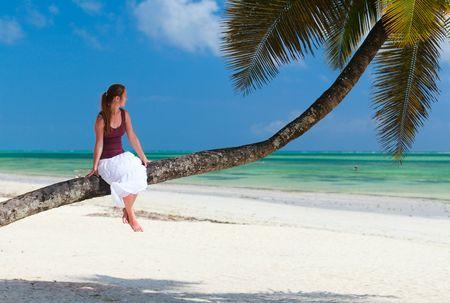 Woman sitting on palm tree on exotic beach of Zanzibar island photo