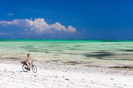 zanzibar: Jonge man fietsen langs tropische strand van Zanzibar eiland