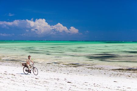 Young man bicycling along tropical beach of Zanzibar island photo