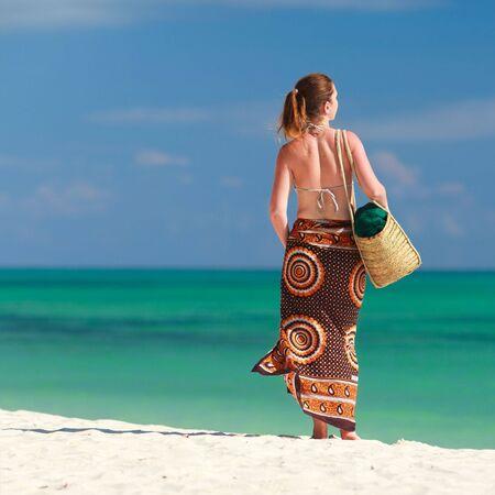 Beautiful girl with beach bag on tropical beach of Zanzibar island