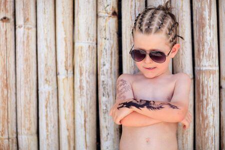 tatouage dragon: Gar�on Mignon 5 ans avec africaine de coiffer les cheveux et le tatouage henn�