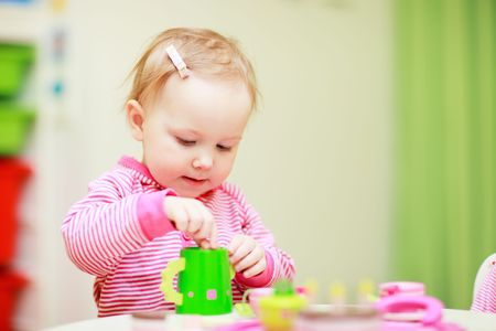 Adorable little girl playing with toys in her room photo