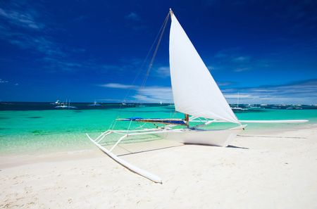 White sailboat on perfect tropical white sand beach in Boracay, Philippines photo