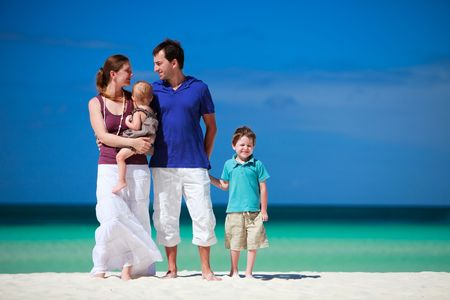 Family with two kids on white sand tropical beach Stock Photo