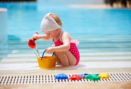 Cute toddler girl playing in swimming pool